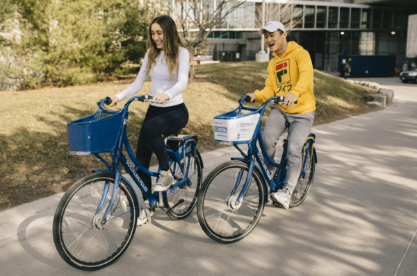 Two Innovation by Design Students Riding Bikes